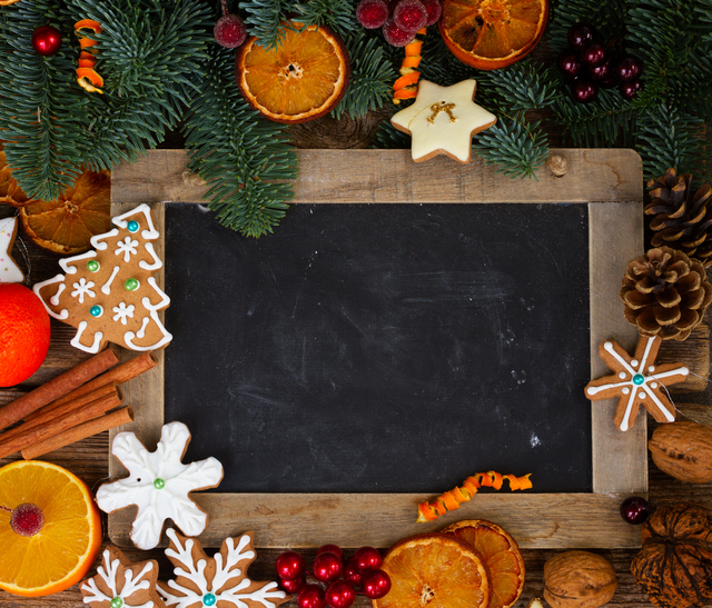 christmas gingerbread cookies with fir tree twigs frame with empty black chalkboard