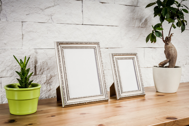 wooden shelf with frames and flowers against a brick wall