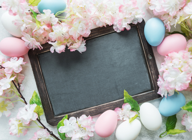 Easter card with old blank chalkboard surrounded by pink flowers and colorful Easter eggs